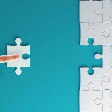 finger pushing last piece of jigsaw into puzzle