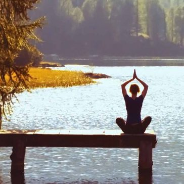 Person doing yoga by the water